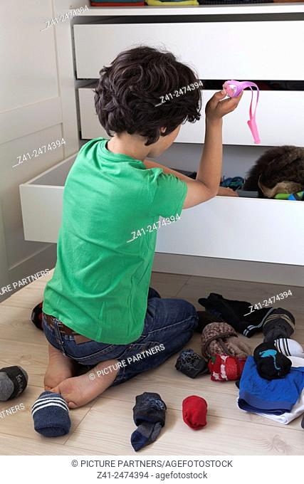 Teenage boy making a mess while searching into his wardrobe drawer