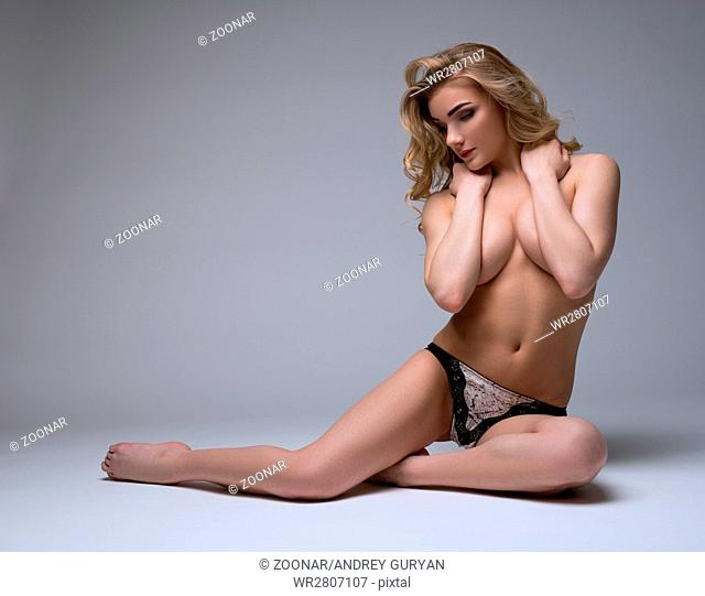 Topless blonde covering her breasts with hands