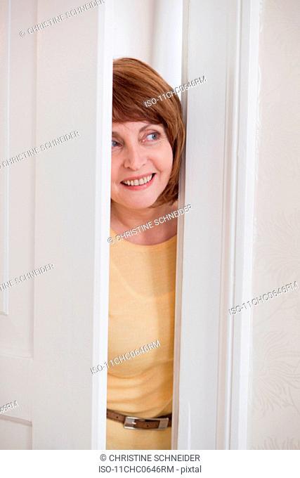 woman smiling looking through a door gap
