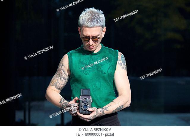 Tattooed man holding vintage camera
