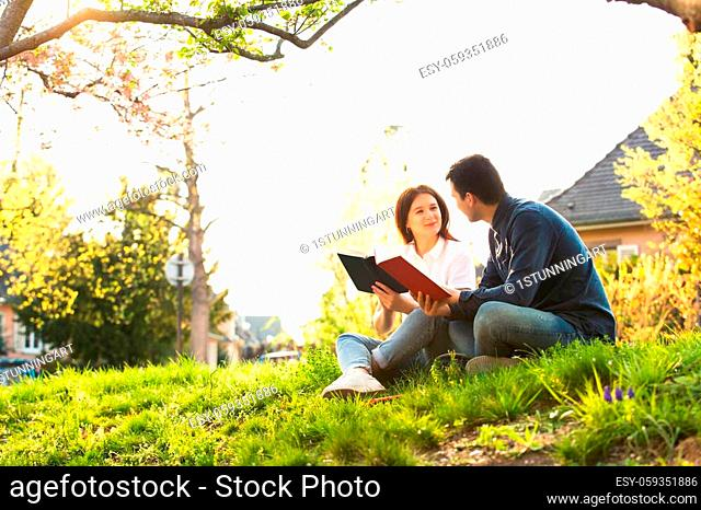 Students learning for exam together in a city park. Students Brainstorming Meeting learning for exam. Fast learning concept. Students Teamwork