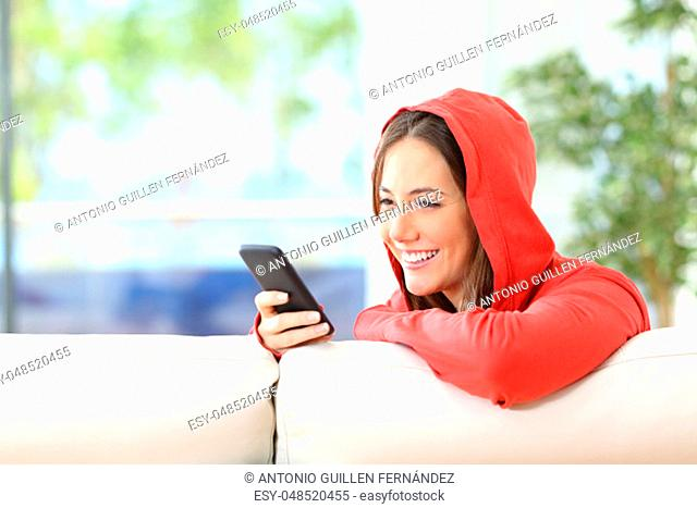 Happy teenager girl in red using a smart phone sitting on a couch at home with a window with a green background outdoors