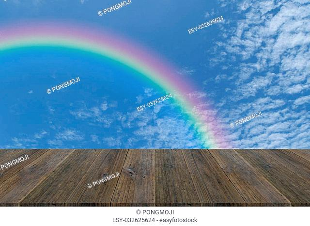Wood terrace and Blue sky and white cloud with rainbow
