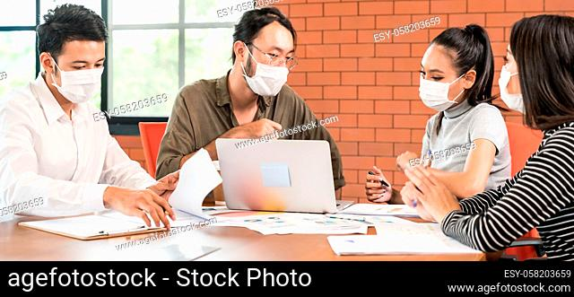 Panoramic group of asian caucasian business team meeting and brainstorm in meeting room after office reopen, they wear protective face mask as new normal...