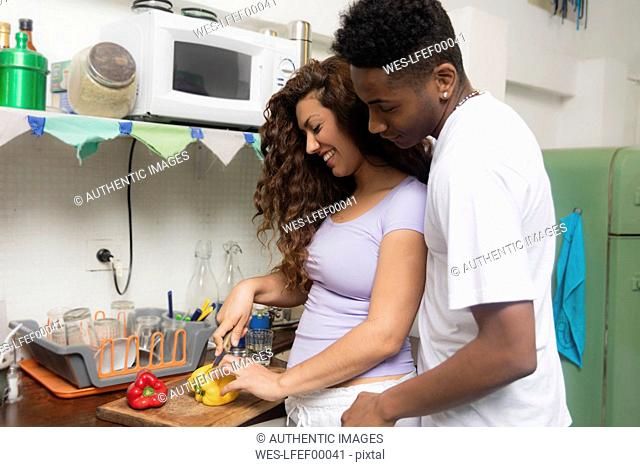 Happy young couple in love preparing food in the kitchen