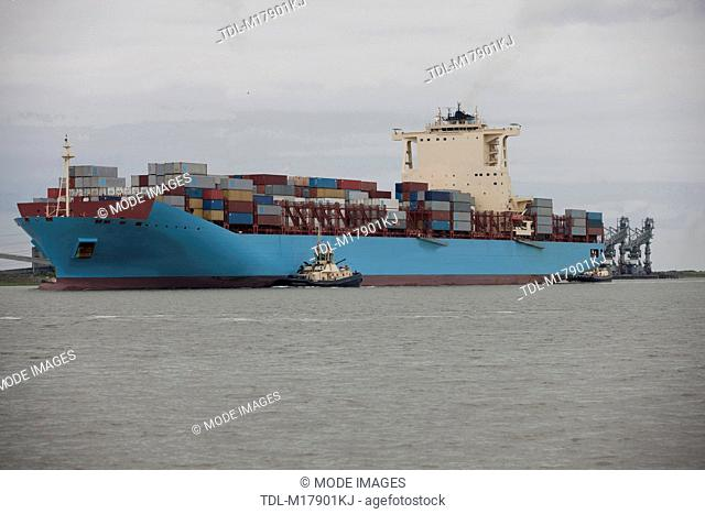 A container ship being escorted to port by tug boats