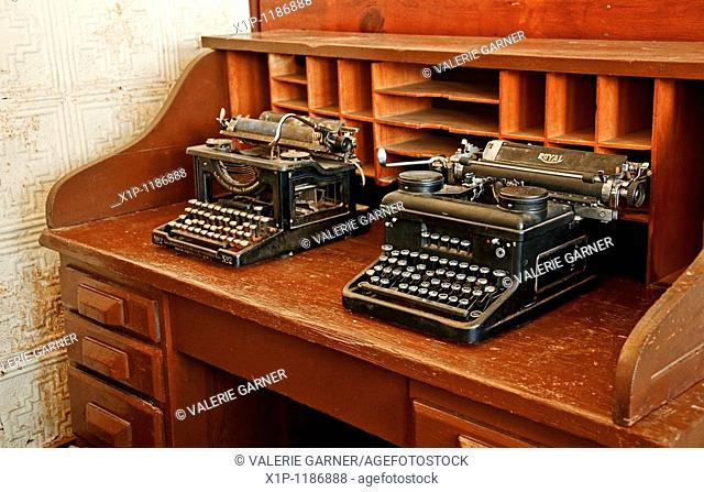These two antique black typewriters are sitting on a vintage turn of the century wooden desk, along with vintage wall paper in the background for this past era...