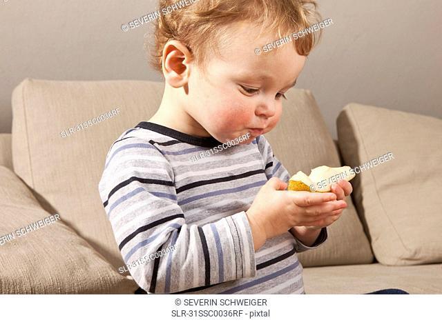 Little boy eating pear