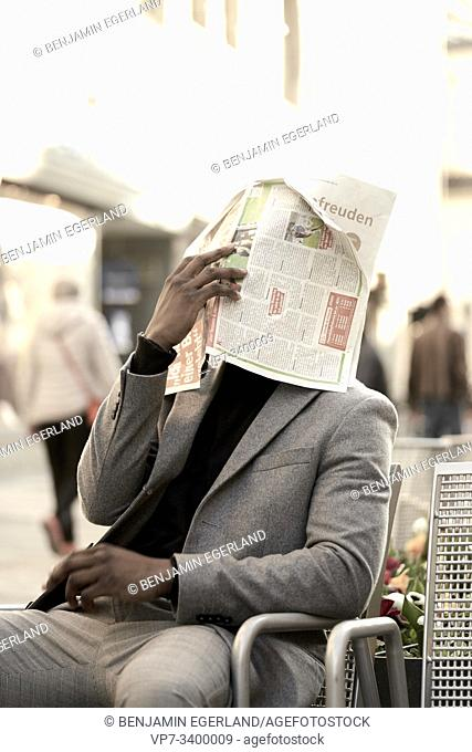 Young African man sitting on chair, covering his face with newspaper, in Munich, Germany