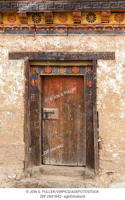 Traditional Bhutanese farm houses are built of packed mud, with very thick walls. Punakha, Bhutan. Detail of door