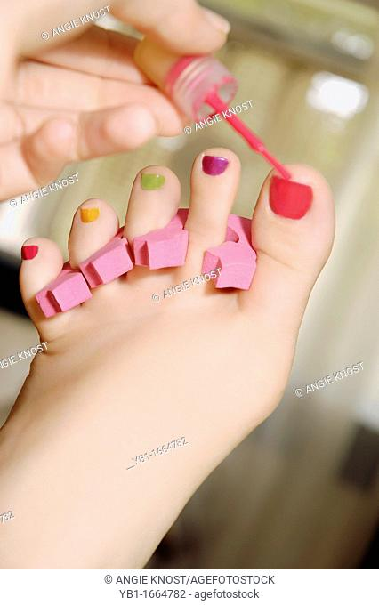 A woman's hand is painting her toenails in various bright colors with nail lacquer