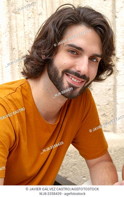portraits of a young man on street, looking at camera while smile with a t-shirt orange