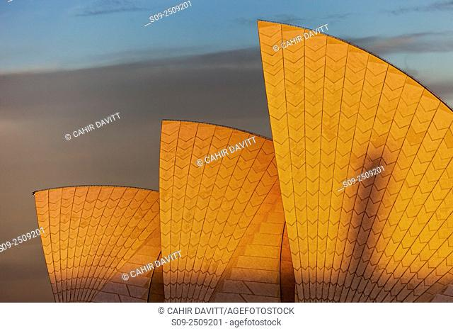 The sails of the Sydney Opera House, Designed by the Architect Jorn Utzorn glow in the light of the setting sun, Bennelong Point, viewed from the Rocks, Sydney