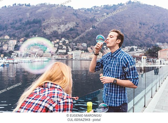 Young couple on waterfront blowing bubbles, Lake Como, Italy