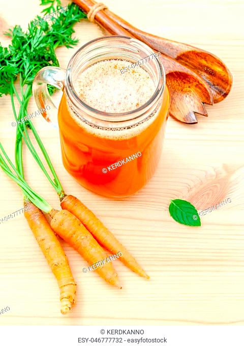 Glasses of carrot juice with carrot roots on wooden background.Glasses of tasty fresh carrot juice.Carrot juice and carrots