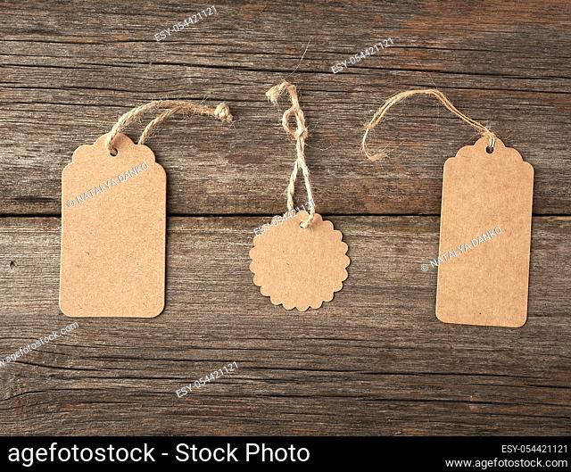 Empty brown paper tag tied with white string. Price, gift, sale tag on the gray wooden background, close up