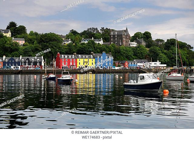 Colorful houses reflected in the water of Tobermory harbour on the Isle of Mull with moored boats Scottish Inner Hebrides Scotland UK