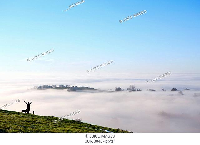 Dog and person standing on hill over fog covered valley