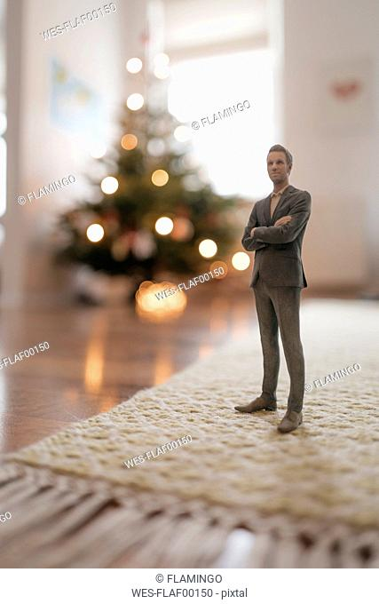 Businessman figurine standing next to a Christmas tree at home
