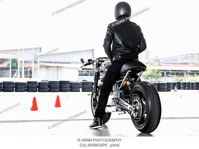 Man getting ready to test electric cafe racer motorbike on race track