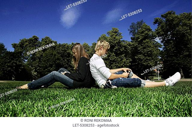 Teenaged girl and boy on vacation  Frendship  Mobile phone  Checking text messages