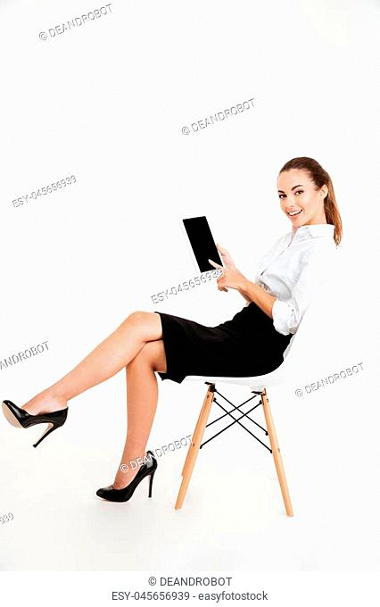 Portrait of a smiling businesswoman sitting on the chair and pointing finger at blank screen tablet computer isolated on a white background