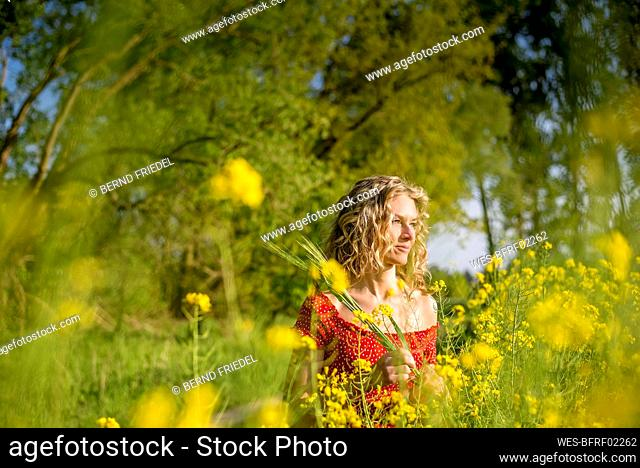 Thoughtful beautiful woman with curly hair standing amidst oilseed rapes