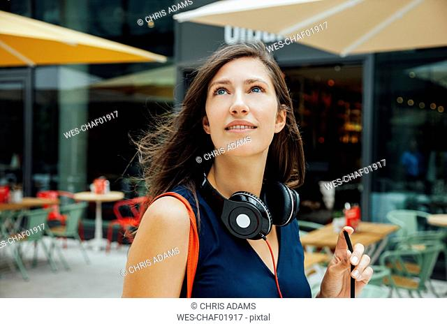Portrait of smiling young woman with headphones and takeaway drink in the city