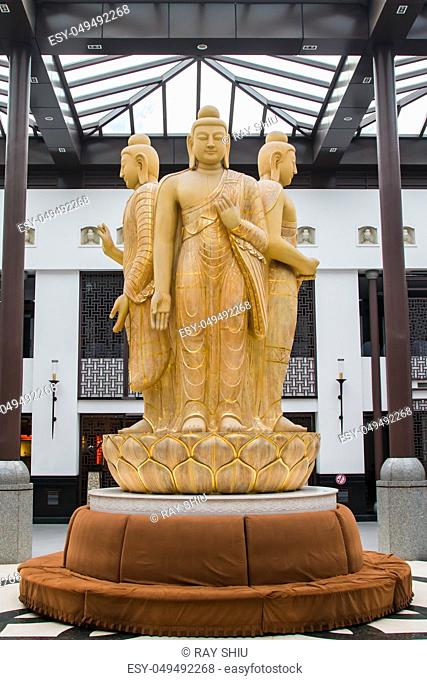 A golden statue of 3 buddhas in the hall before advancing to the Yungang Grottos