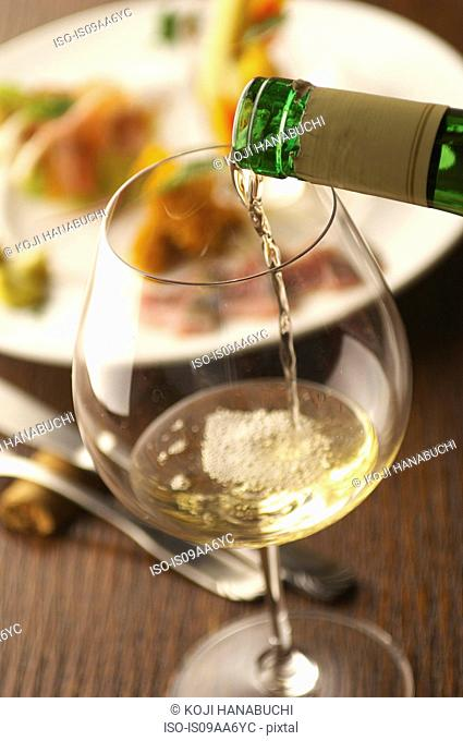 Still life of white wine pouring into glass
