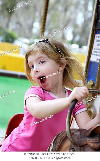 funny happy gesturing little blond girl playing on horses merry go round