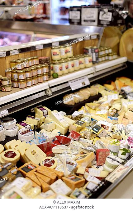 Variety of cheeses in a fridge of a farmer's market grocery store Canada
