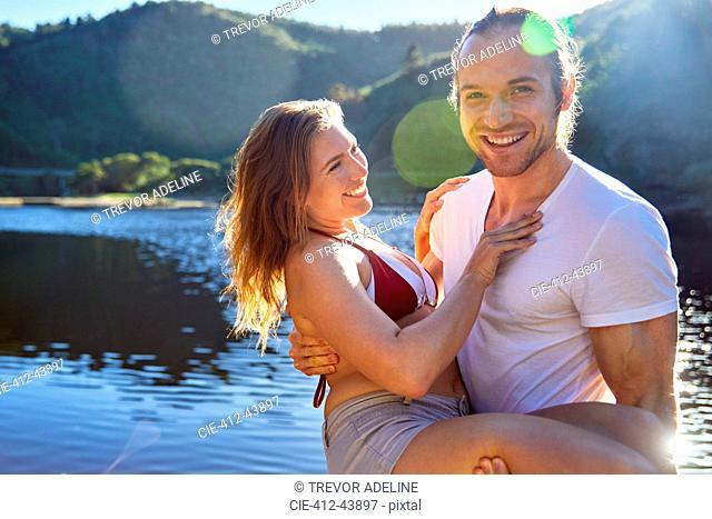 Portrait romantic, carefree couple at sunny summer lake