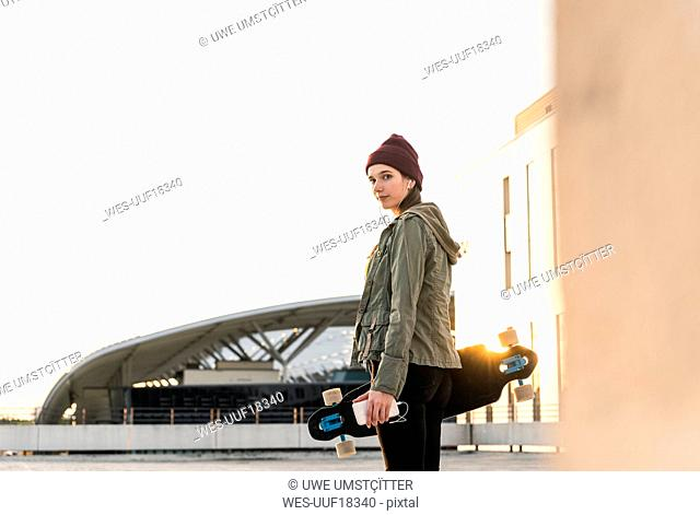 Stylish young woman with skateboard on parking deck
