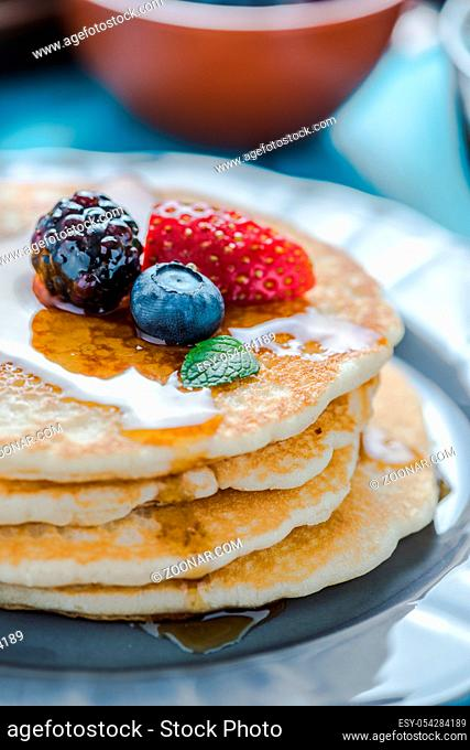Close view on pancakes stack with fruit and honey