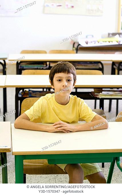 Boy sitting in empty classroom, looking at camera
