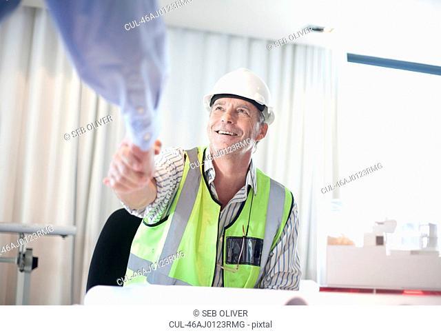 Businessmen shaking hands at desk