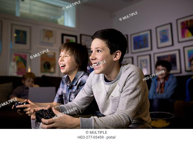 Smiling boys playing video game in living room