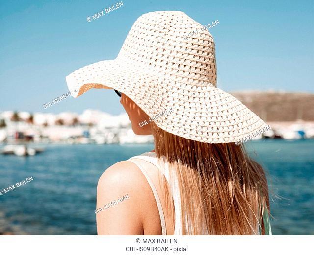 Rear view of woman wearing sun hat, Menorca, Spain