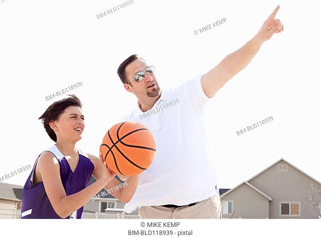 Father teaching son to play basketball in driveway