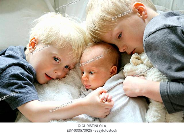 Two young children, a toddler and his big brother are lovingly hugging their newborn baby sister., and holding hands