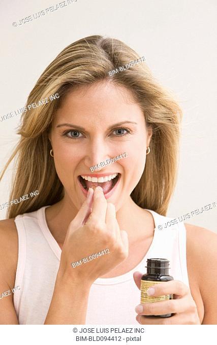Smiling Caucasian woman taking pill