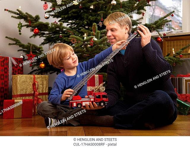 father, son play with christmas present