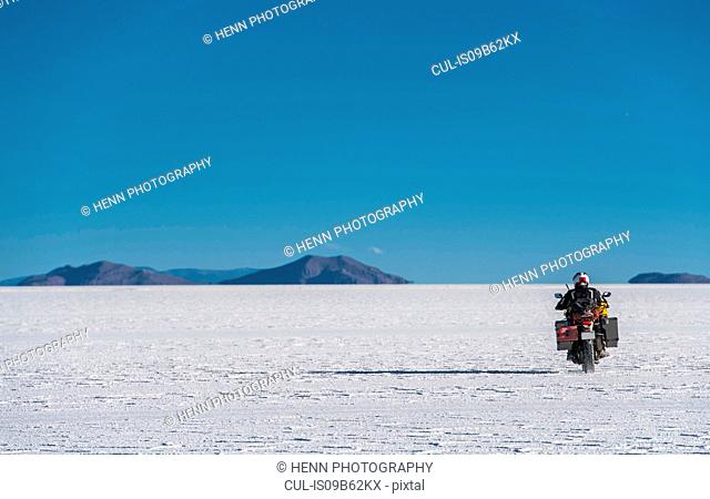 Man riding motorcycle on the salt flats of Uyuni, Potosi, Bolivia, South America
