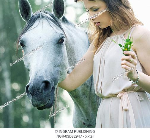 Young lady stroking spotted horse
