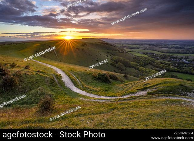 Sunset over Fulking village and views towards truleigh hiill and the sea on the South Downs National Park from Devil's Dyke, Sussex, England