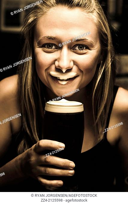 Fun lifestyle image of a paddy woman imitating an Irish man when drinking dark ale beer leaving a foam moustache. St Patrick's day concept