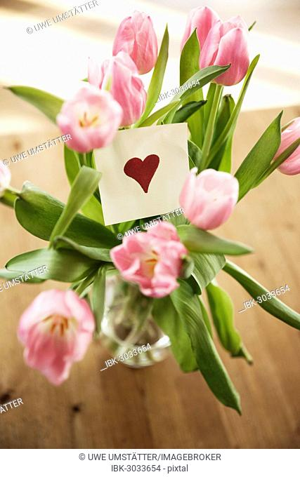 Tulips in vase, paper note with a heart, Mannheim, Baden-Württemberg, Germany
