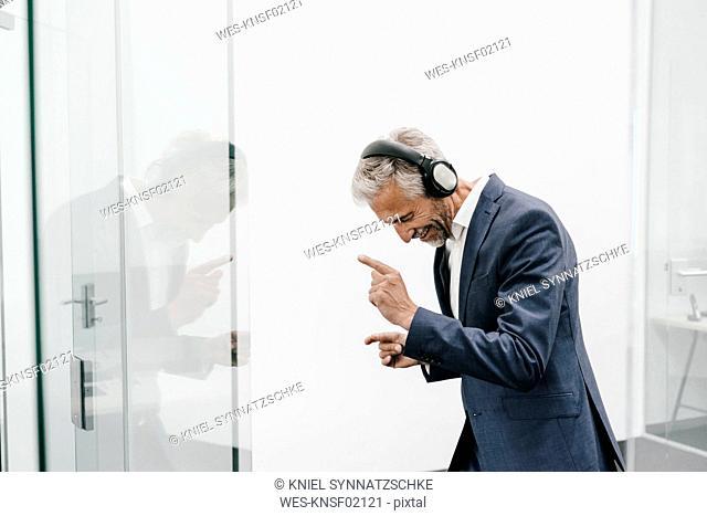Happy mature businessman in office wearing headphones