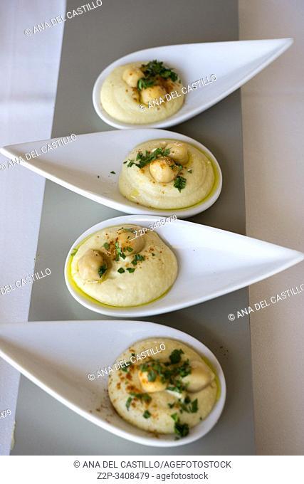Hummus on four porcelain spoons in gourmet restaurant